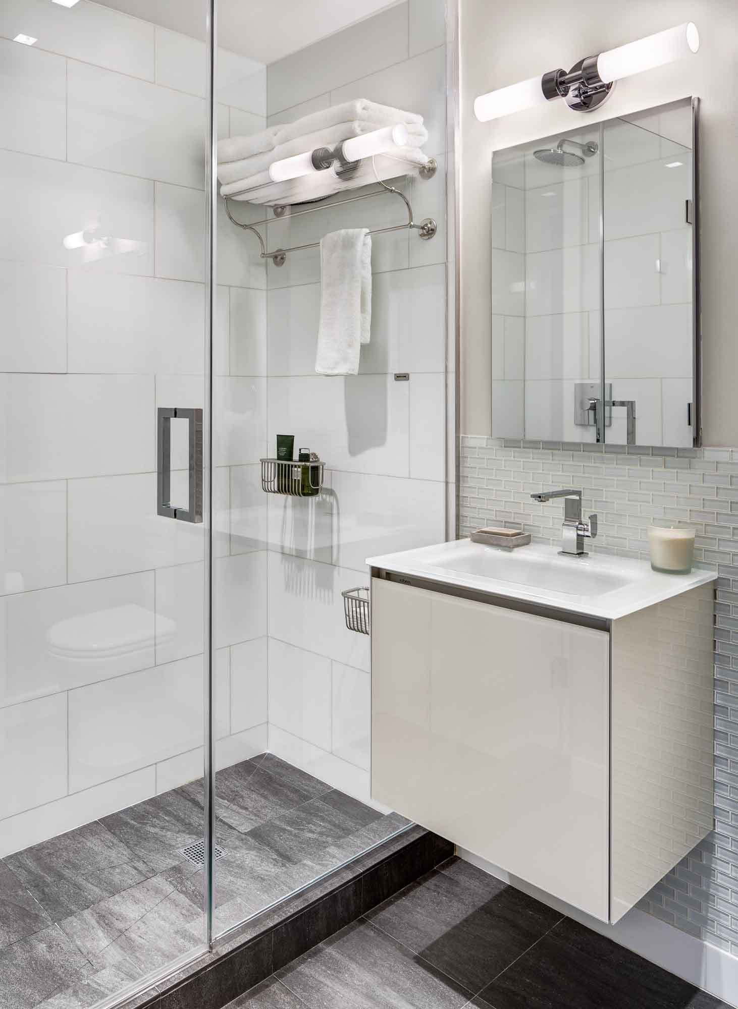 The abundance of sparkling surfaces adds a high style to the interior of this bathroom. A few elegant small lamps are used in this bathroom, the light from which is perfectly reflected by polished, mirrored and glass surfaces. This reflection makes the bathroom look bright. In addition, the white surfaces create a sense of space. If you are looking to improve your bathroom interior design, then do it the right way by choosing one of the leading design studios in New York – Grandeur Hills Group.