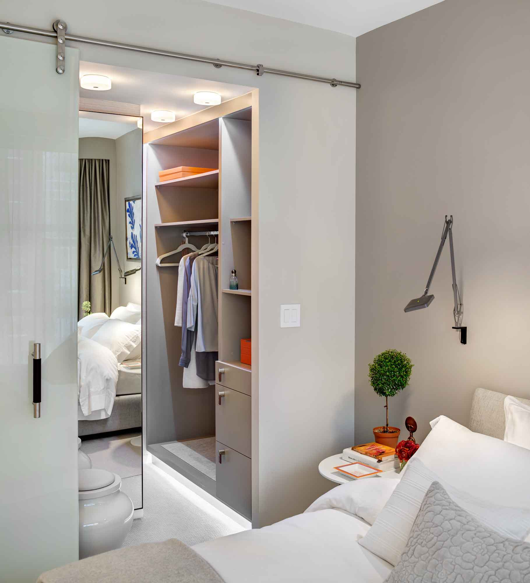 Take a look at this stylish closet. Despite its large size, it does not take up much free space. On the other hand, the closet adds some functionality and high style to the bedroom interior next to it. When you look at this closet, you see that the closet is kind of built into the wall, does not bulge out and does not take up much free space. This closet fits harmoniously into the interior of this apartment not only in size but also in color. You can add some functionality and high-style to your own bedroom interior as well by placing a stylish and beautiful closet next to your bedroom. Contact our design studio in NYC and order our professionals who are bound to know the shortest way to beauty and functionality!