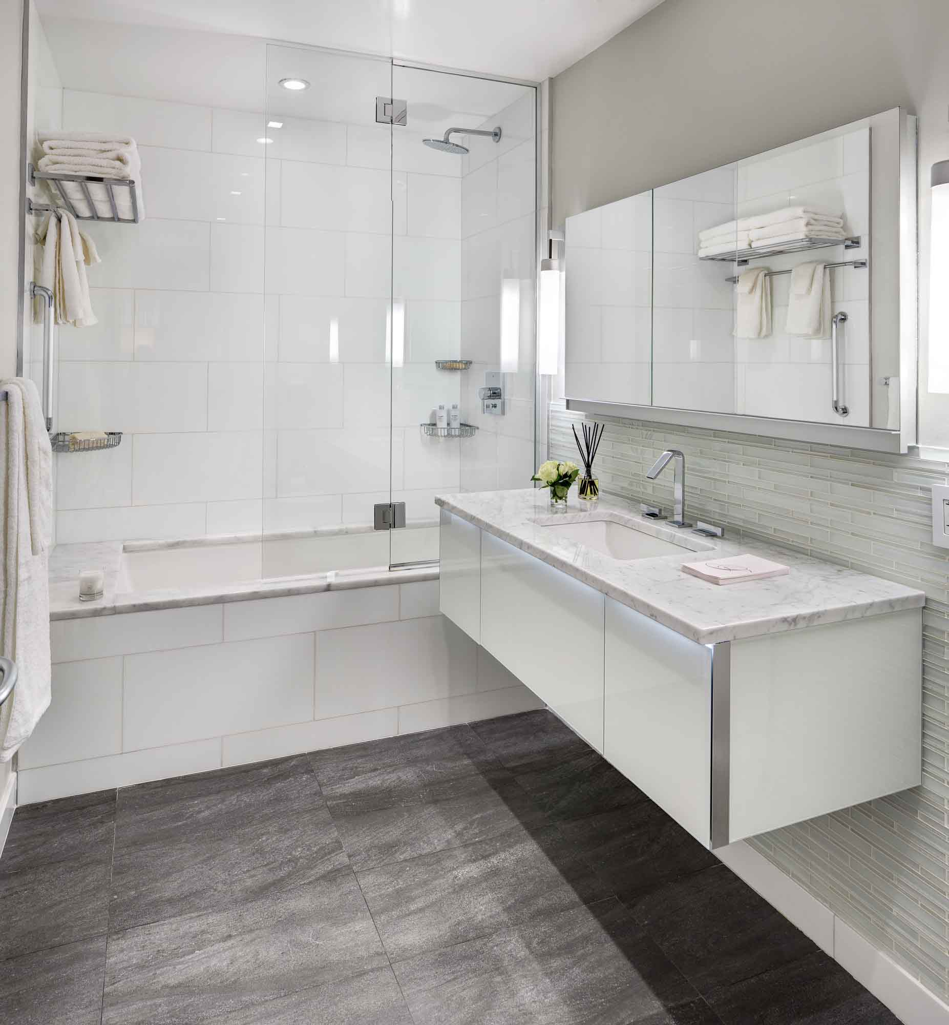 This bathroom looks very bright and spacious, doesn't it? The bathroom is lit by several miniature ceiling-mounted lamps. Pay attention to the large number of glass, polished and mirrored surfaces that not only add shine to the interior, but also visually expand the room. The dominant color here is white, which perfectly reflects the light emitted by the fixtures, also making the room bright and spacious. Don't miss the chance to elevate your bathroom interior design together with the best Grandeur Hills Group specialists