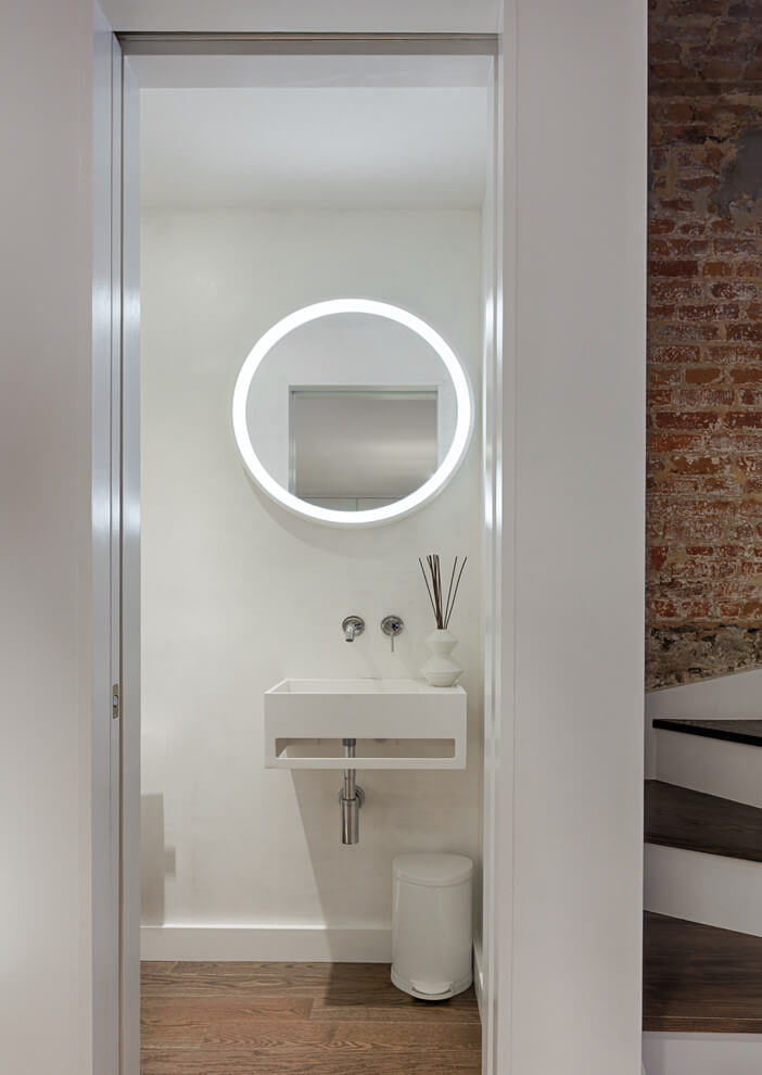As you can see the prevailing color in this powder room is white. Thanks to the white color, the room is literally filled with light and looks welcoming, light, clean, and spacious. Traditionally, the floor is decorated in darker color that greatly contrasts with the snow white walls and ceiling. The oval mirror above the wall-mounted sink creates a magic atmosphere in this powder room thanks to both its size and its unusual form. Looking for unusual interior design ideas for your home to stand out? Contact our outstanding interior designers and make your home look impressive!