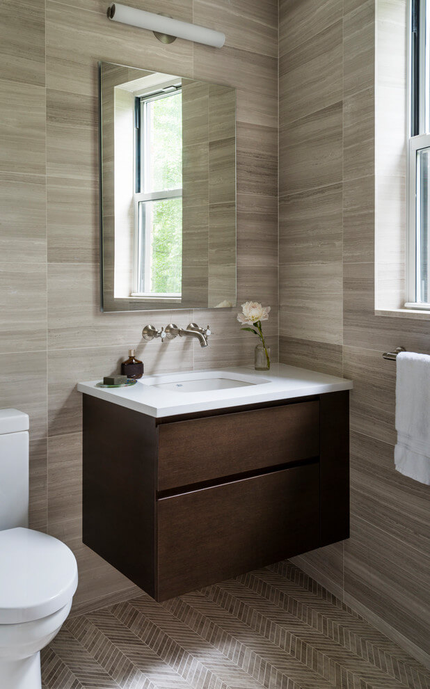 This powder room is decorated in unusual dark colors that evoke a feeling of comfort and warmth. Despite the abundance of dark surfaces, the room does not seem dull and cramped thanks to the large window, stylish mirror, and sparkling tile surfaces that perfectly reflect the rays of daylight. Our interior designers placed here only the most necessary furniture pieces so as not to clutter up this powder room. Don't miss the chance to elevate your powder interior design as well together with the top Grandeur Hills Group interior designers!
