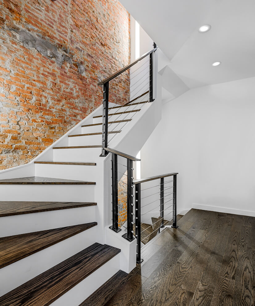 This chic staircase is one of the most attractive elements in this home. Pay attention to the width of the staircase. This width makes the staircase seem majestic. However, besides it there are other features that strongly influence the perception of this staircase. One of the most important features is the strong color contrast of the walls. Some of the walls are decorated in a bright brick color, whereas the others are painted white. The white color symbolizes the natural beginning, the sensation of which is enhanced by natural materials - chrome steel and wood, of which this staircase is made. Don't forget to contact the leading design studio in NYC and order the high-quality interior design service to radically change your home look!