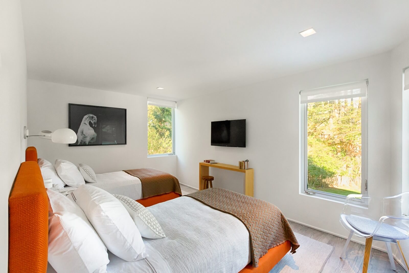 This comfortable bedroom is decorated in white colors that add warmth, tenderness, cleanliness and peace to the whole interior. Note the orange color of the beds and some black paintings on the walls that act as impressive decorative elements. Colorful furniture pieces and decorative elements create a lively atmosphere, bringing an optimistic and cheerful mood to the owners of the bedroom. Try one of the best Grandeur Hills Group interior design service and appreciate the high quality of the work of our interior designers!