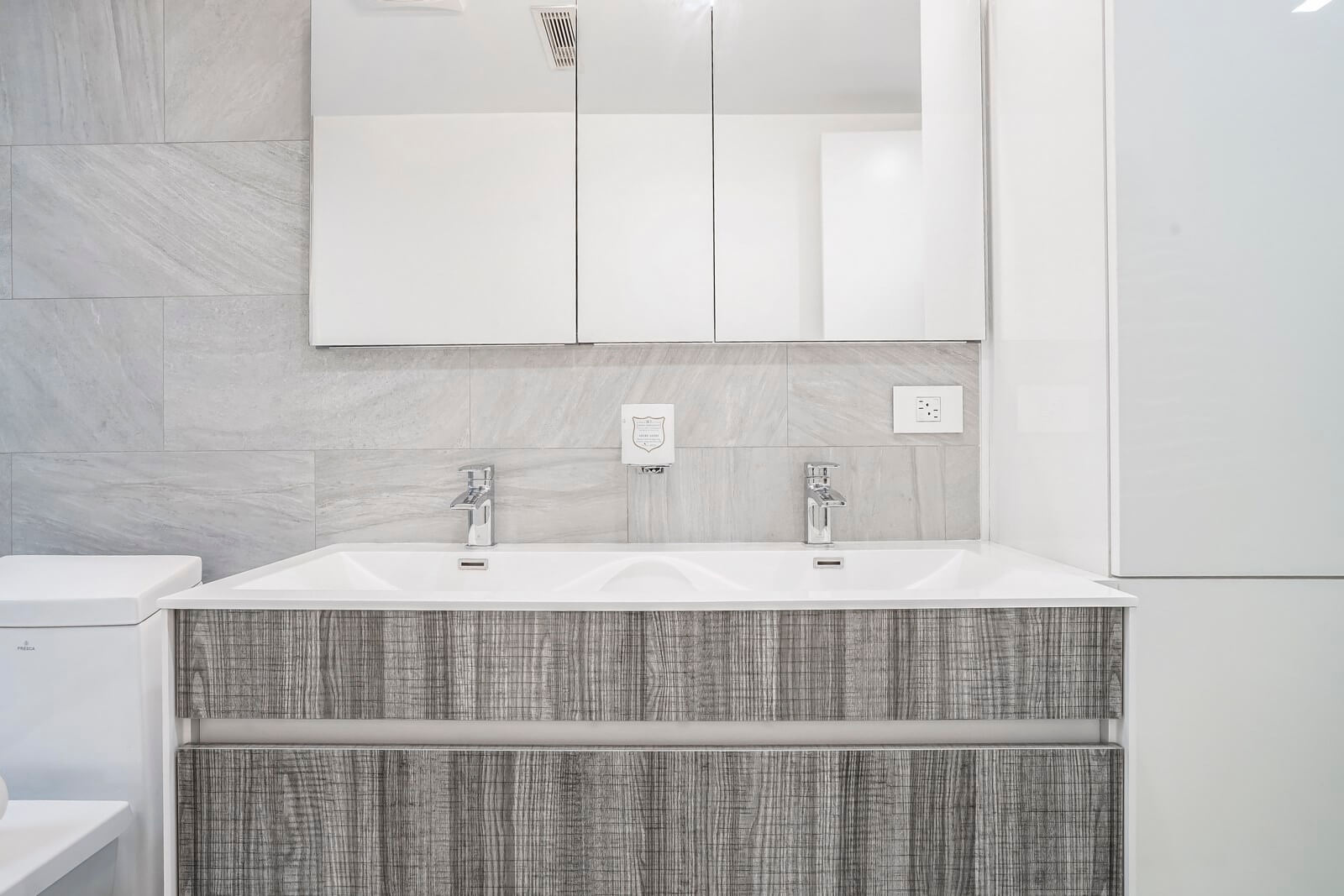 This bathroom area is equipped with contemporary sanitary engineering and stylish furniture pieces, including countertops and vanities. The walls are finished with nice-looking large tiles. Several wall-mounted power socket make the bathroom very comfortable and fully functional. The bathroom is decorated mostly in white and gray colors and their shades, which perfectly harmonize with each other, creating a welcoming, warm and cozy atmosphere in the bathroom. Don't hesitate to make your bathroom as fully functional and attractive as this one in the photo with our top interior designers!