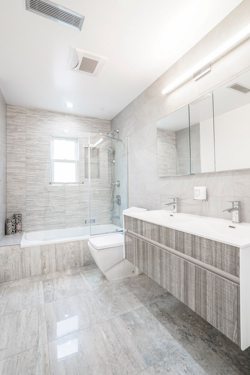 Contemporary air conditioning, many large mirrors, stylish fixtures embedded in the ceiling, an abundance of beautiful sparkling and glass surfaces, and plenty of free space are the key features of this luxurious bathroom. The bathroom is literally flooded with light thanks to several powerful original fixtures built into the walls and ceiling. The dominant color of the interior is white, which is in perfect harmony with most other colors, including gray, in which the floor and some of the furniture pieces are decorated. Make your bathroom interior as beautiful and fully functional as this one in the photo! Grandeur Hills Group is always ready to help you with it!