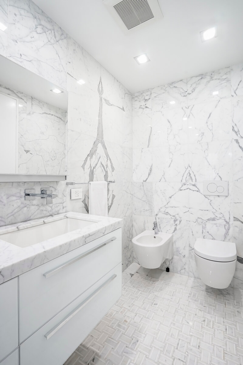 The bathroom is totally decorated in white that hints at freedom, spaciousness, calmness, independency, warm, and comfort. All interior pieces including sanitary engineering are put around the perimeter of the bathroom. This fact makes the bathroom spacious and bright. Besides, some beautiful large fixtures add light and shine to the interior. Also, pat attention to the amazing walls with small abstract patterns. Thanks to them, the bathroom interior looks kind of mysterious. Elevate your bathroom interior as well with one of the most prosperous NYC design studios – Grandeur Hills Group!