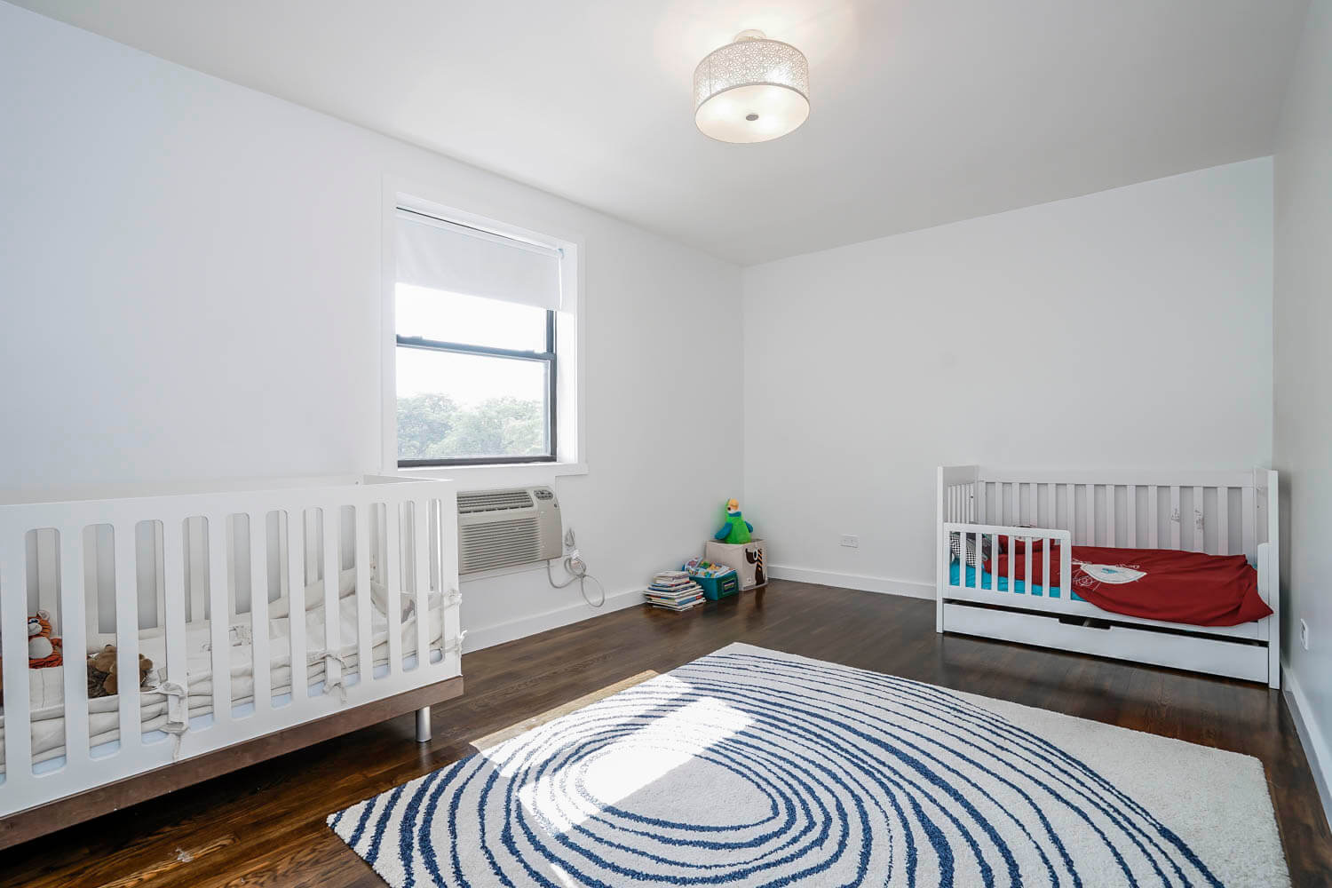 This beach-style kid's room looks very bright, fresh, and spacious thanks to a few large windows through which light and clean fresh air can easily enter the room, a small number of furniture pieces placed mainly around the perimeter of the room, and light colors, which create a welcoming, warm and cheerful atmosphere. Change radically the look and functionality of your kid's room, too, together with our top NYC interior designers!