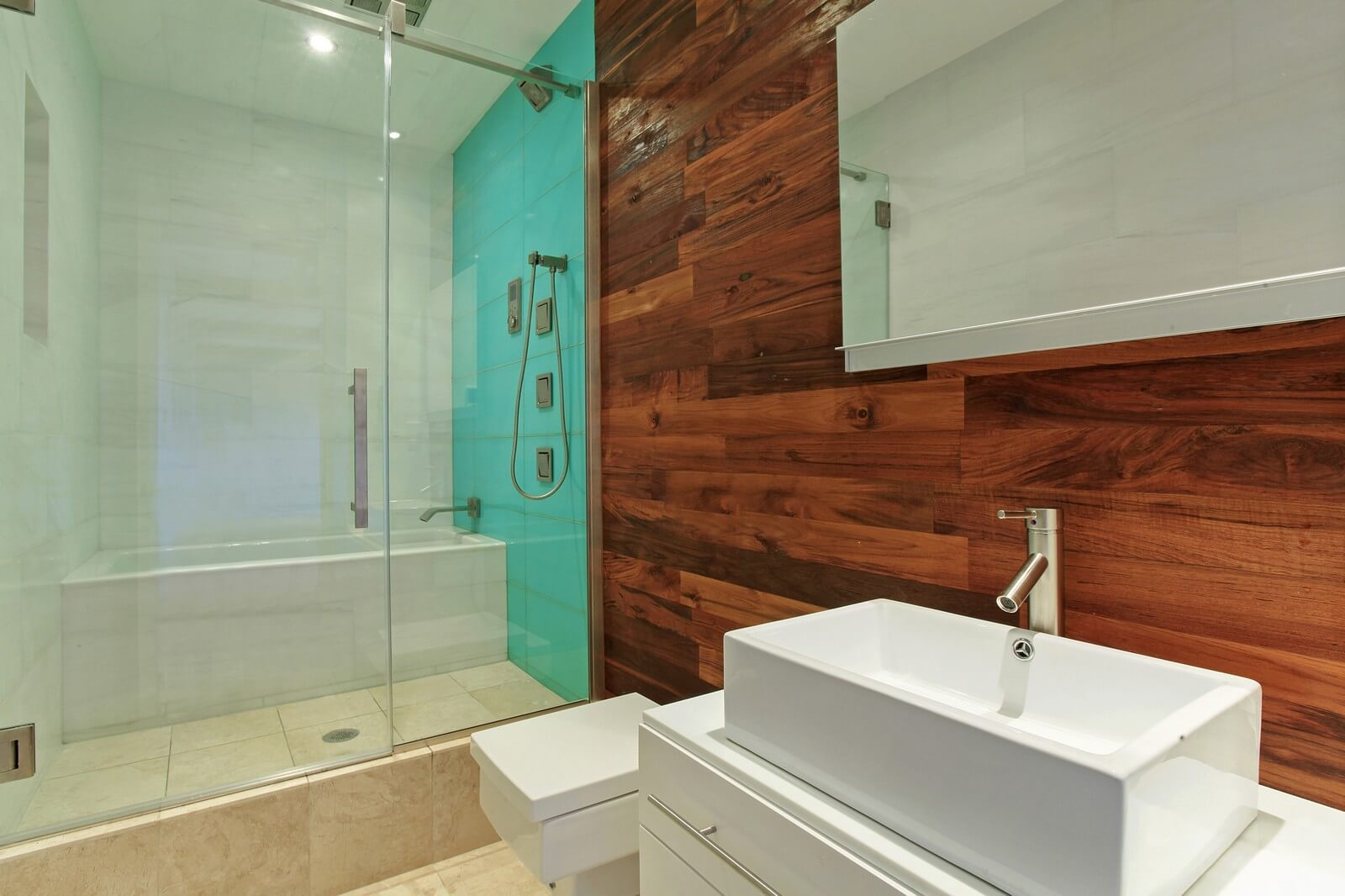 This bathroom looks very beautiful, isn't it? Why do we find it fine? Contemporary sanitary engineering hints at comfort, high quality ECO-friendly finish makes the bathroom look attractive. Pay attention to the use of the aquamarine color. This fine color is known to be associated primarily with water. The wall decorated in aquamarine blends perfectly with both the freestanding bathtub of snow white and glass surfaces of the door and window. Do you need radical changes in your condo interior design? Our team of professional interior designers is always ready to help you make your facility stand out!